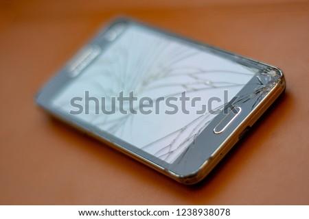 Broken screen mobile phone on orange background