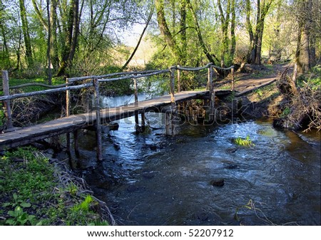 Broken small wooden bridge across the water