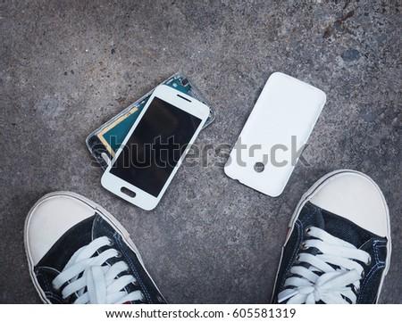 Broken smart phone after being dropped on concrete grunge floor between owner's sneaker shoes