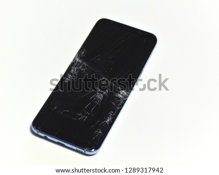 Broken smartphone isolated on a white background. The screen of the phone is broken and scratched.