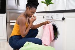Broken Smelly Washing Machine. Woman Washing Towel
