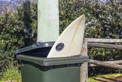 Broken surfboard in a rubbish bin