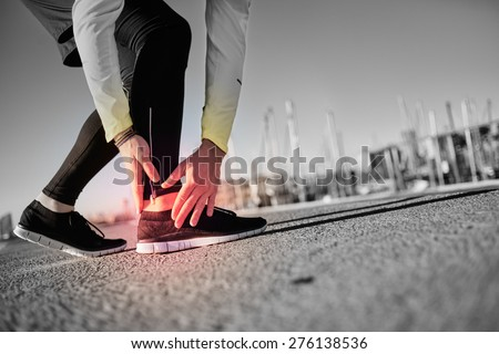 Broken twisted ankle - running sport injury. Athletic man runner touching foot in pain due to sprained ankle.
