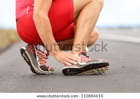 Broken twisted ankle - running sport injury. Male runner touching foot in pain due to sprained ankle. - stock photo