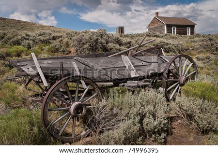 Broken wagon sits downhill from the log school in the ghost town of South Pass City at the South Pass City State Historic Site in Wyoming