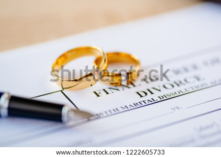 Broken wedding rings on divorce decree. Divorce, separation and family law concept #1222605733