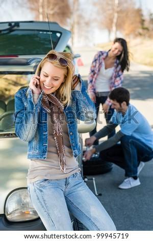 Broken wheel man changing tire help two female friends