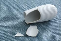 Broken white ceramic vase on grey carpet, closeup