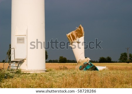 broken wind turbines on green field. Alternative source of energy