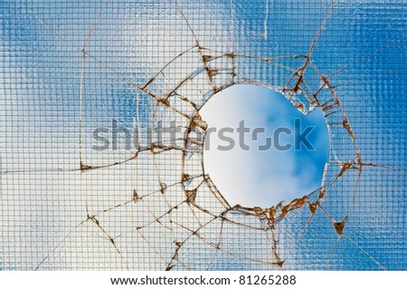 Broken window glass - cracked with hole over blue sky.