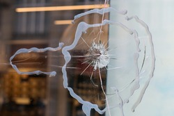 Broken window glass of a store located in downtown Zürich, Switzerland. Crushed and shattered glass, hopefully the insurance will cover the damage. Concept of stealing, criminal activity and security.
