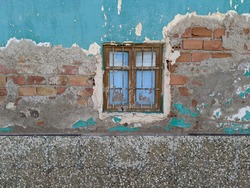 broken window in the center of abandoned and dilapidated facade