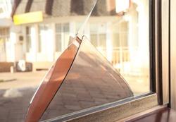 Broken window with sharp smithereens outdoors. Requiring repair