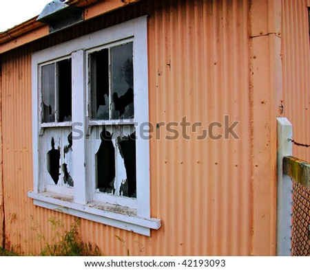 Broken windows of a derelict orange hut