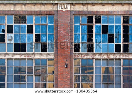 Broken windows on old derelict building with reflections