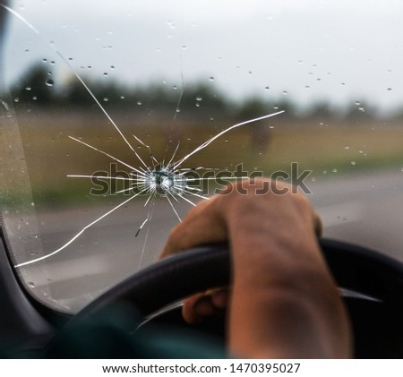 Broken windshield of a car. A web of radial splits, cracks on the triplex windshield. Broken car windshield, damaged glass with traces of oncoming stone on road or from bullet trace in car glass