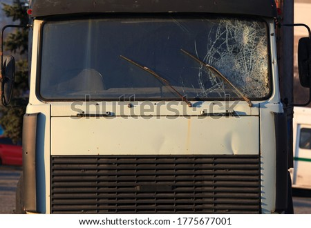 Photo of  Broken windshield of a truck (lorry). Accident and traffic accident. The crash. A gunshot attack on a car. Abandoned truck after an accident