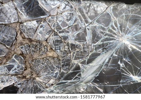 Photo of  Broken windshield thick glass after car crash. Bullet-resistant glass (ballistic or transparent armor). Сonsequence of road incident. Traffic collision. Lethal head-on collision involving two vehicles