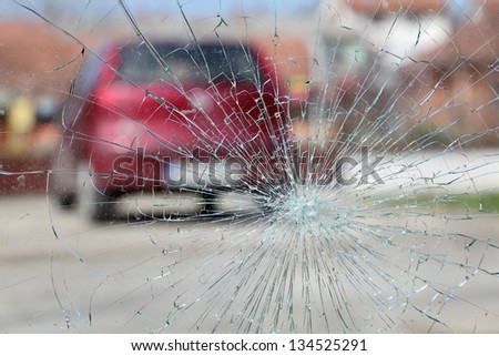 Broken windshield with red car in background, selective focus