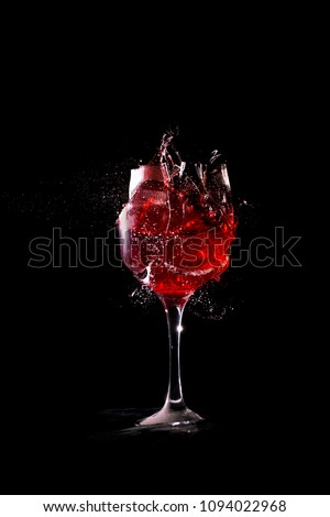 Broken wine glass on black background.Red wine