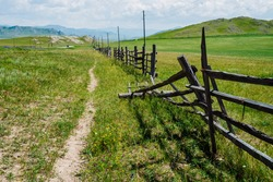 Broken wood fence and poles with wires along vast field in mountains in sunny day. Beautiful sunny alpine landscape with asphalt road along field behind long fence in highlands. Vivid mountain scenery
