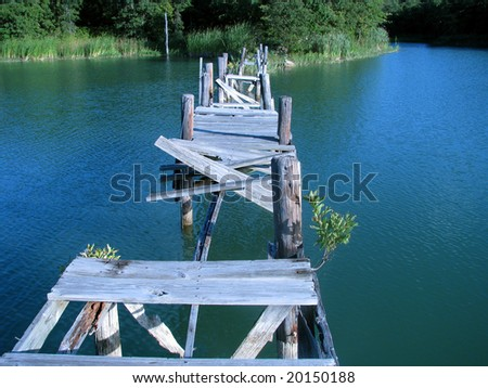 Broken wooden  bridge after disaster over quiet lake depicting a danger trap. - stock photo