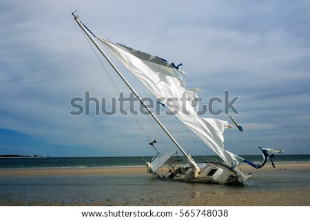 Broken yacht with a torn sail aground. Gulf Coast, Florida, St.  George Island