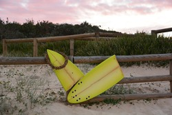 Broken yellow surf board with reed wreath around it tied to a wooden fench on the edge of the beach and the dunes at sunset