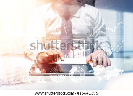 Broker consultant with charts using tablet at office desk to make a stock exchange deal. Double exposure