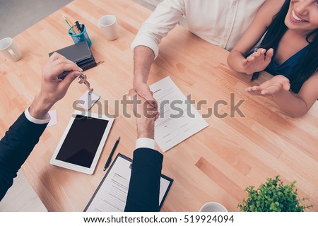 Broker giving keys of new house and handshaking with customer