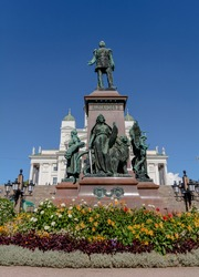 Bronze Alexander II memorial at the Senate Square. Monarch's figure stands on red granite pedestal surrounded by symbolic figures representing Law, Light (Science and Art), Peace and Work.