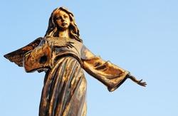 Bronze angel against blue sky in Santa Maria di Leuca, Italy