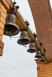 bronze bells hang on a wooden beam on the tower