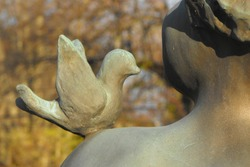 bronze boffin statute from behind of girl with bird on her shoulder