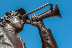 Bronze cast statue with brown patina of an American Civil War soldier playing the bugle.