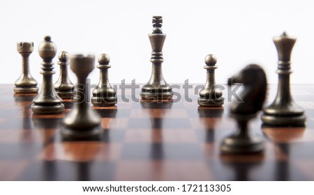 Bronze Chess Set on White Background with Wooden Chess Board, Focusing on King