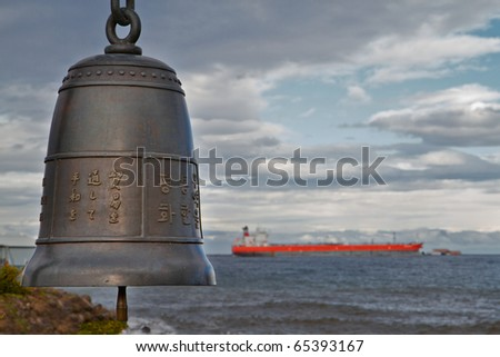 Bronze Chinese Bell with soft focus freighter in background