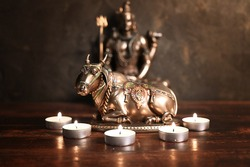 Bronze decoration with cow statue and burning candles on a dark brown background