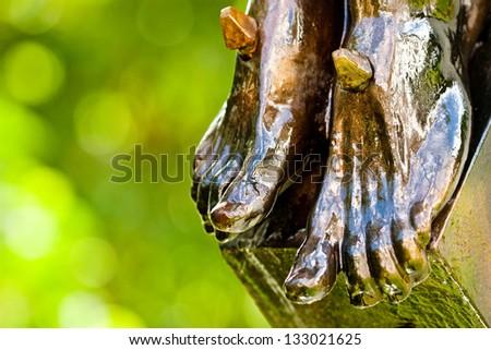 bronze feet of religious statue depicting Jesus Christ