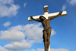 Bronze figure of Jesus Christ on a white wooden cross outside - Hanover, Ontario cemetery on a sunny day