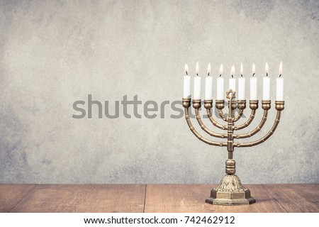Bronze Hanukkah menorah with burning candles on wooden table front old vintage concrete wall background. Holiday greeting card concept. Retro instagram style filtered photo #742462912