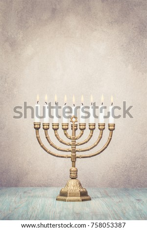 Bronze Hanukkah menorah with burning candles on wooden table front old vintage concrete wall background. Holiday greeting card concept. Retro style filtered photo #758053387
