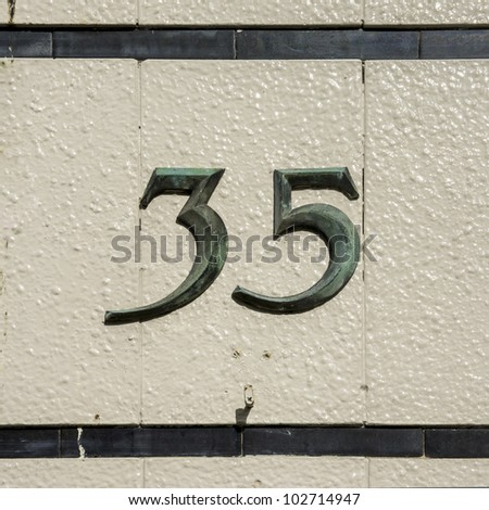bronze house number thirty-five on a wall of ceramic tiles