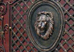 bronze lion head on decorative gate