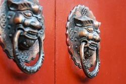 Bronze Lion Head Statue on a Pair of Red Door