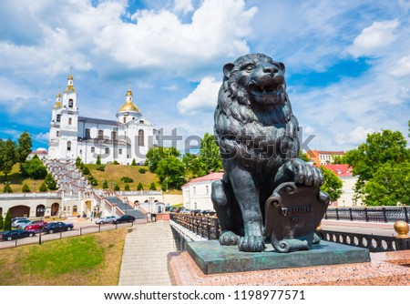Bronze lion on Pushkin bridge in Vitebsk, Belarus with Assumption cathedral on background with selective focus