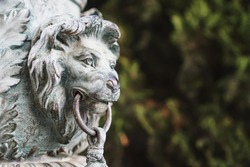 Bronze lion's head made of metal on a column in the Park.
