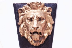 bronze lion's head on the wall of the building