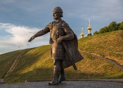 Bronze monument to Yuri Dolgoruky on earthen ramparts background of ancient Kremlin, Dmitrov, Moscow Region, Russia