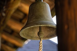 Bronze old metal bell hanged in house entrance outdoors